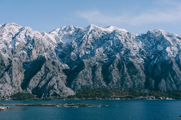 Picos de montanhas cobertas de neve na baía de kotor, montenegro, acima da cidade de dobrota, um assiable e peixes