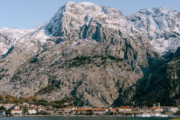 Picos de montanhas cobertas de neve sobre a cidade velha de kotor montenegro baía de kotor
