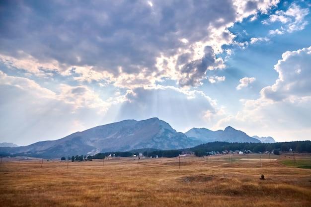 Picos de montanhas e raios de sol atrás das nuvens no céu