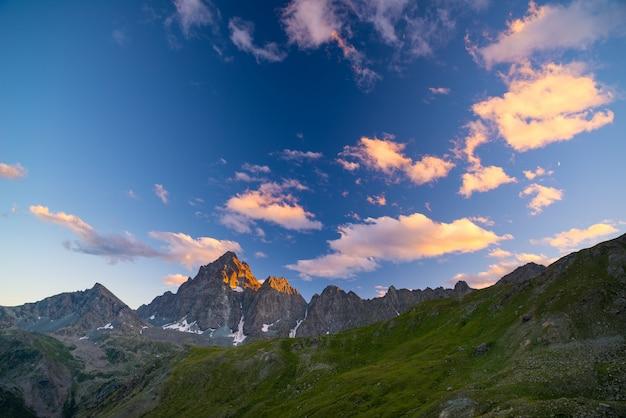 Picos de montanhas rochosas, cumes e vales, os alpes ao pôr do sol.
