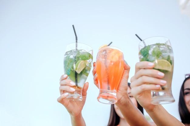 Pictire de mulheres segurar três copos com cocktails. eles mostram para a câmera.