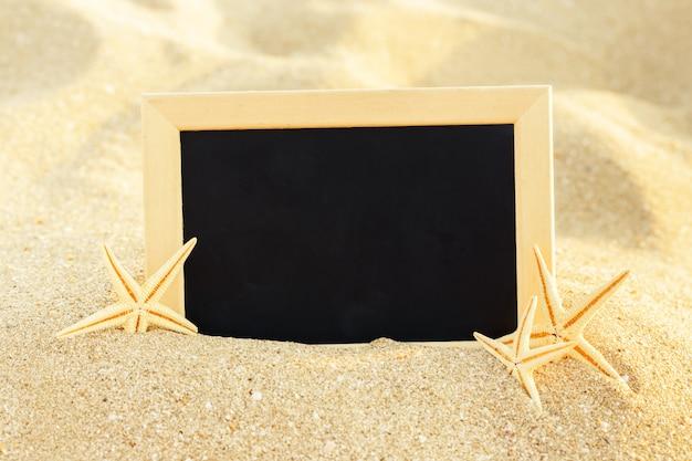 Pictue frame em conchas e fundo de areia. copie o espaço.