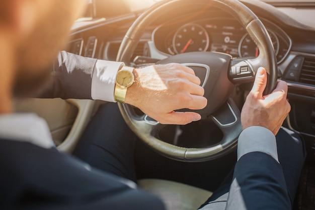 Picutr ofman sentado no carro e olha para os relógios. ele segura uma mão no volante. está ensolarado lá fora.