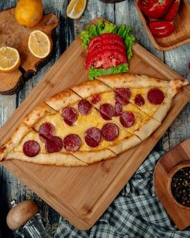 Pide de pizza turca com calabresa, tomate e ervas.
