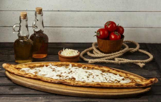 Pide tradicional turca com carne e queijo em uma placa de madeira