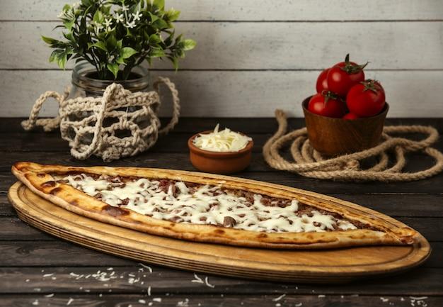 Pide tradicional turca com queijo e carne em uma placa de madeira
