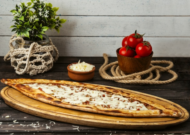Pide tradicional turca com queijo e carne recheada em uma placa de madeira