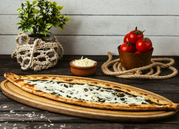 Pide tradicional turca com queijo e ervas em uma placa de madeira