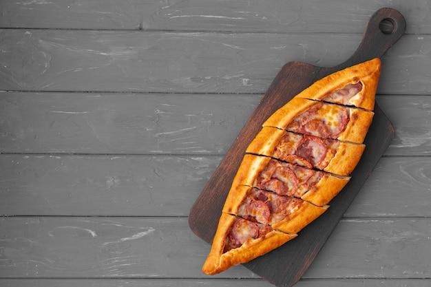 Pide turco recheado de pão achatado na mesa de madeira cinza
