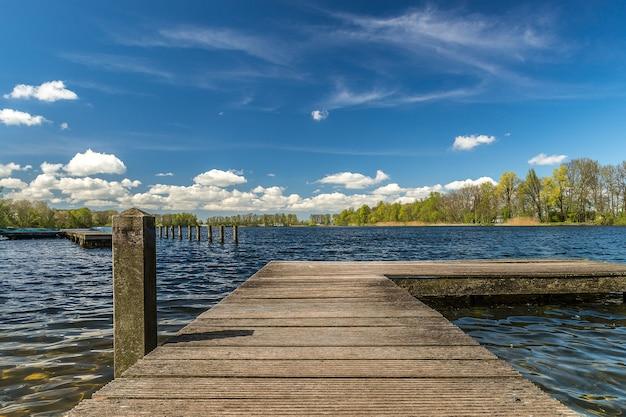 Píer de madeira no mar sob a luz do sol e um céu azul nublado
