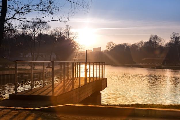 Píer no lago no parque da cidade pôr do sol de outono um lindo caminho de sol na água