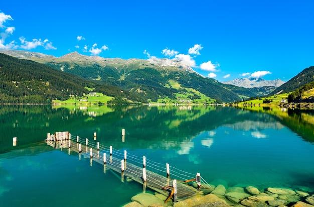 Píer no reschensee, um lago artificial no tirol do sul, nos alpes italianos