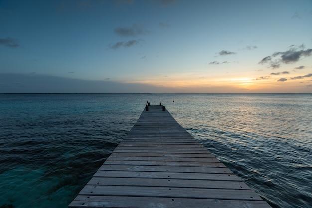 Píer que leva ao pôr do sol de tirar o fôlego refletindo no oceano em bonaire, caribe