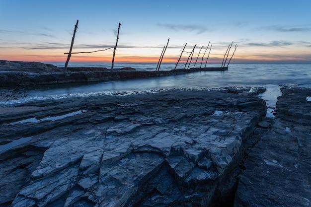 Píer sob o lindo pôr do sol no mar adriático em savudrija, na ístria, croácia