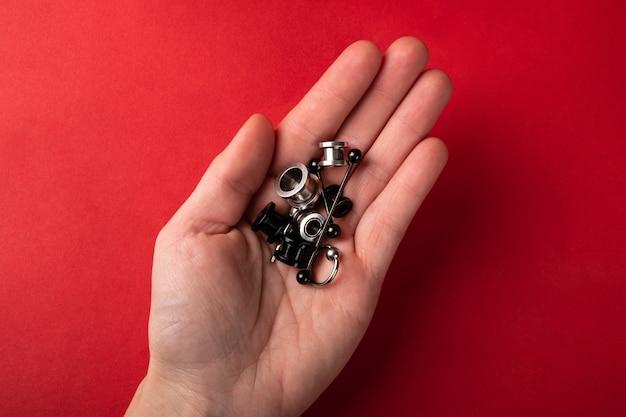 Piercings e joias para as orelhas na palma da mão sobre fundo vermelho