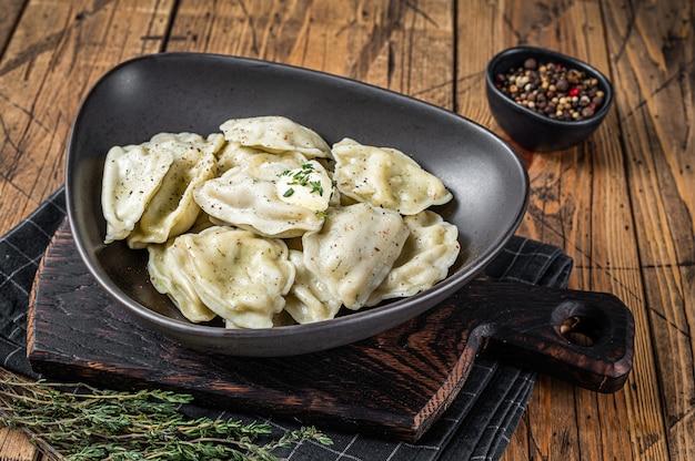 Pierogi de bolinhos de massa com batata em um prato com ervas e manteiga. fundo de madeira. vista do topo.
