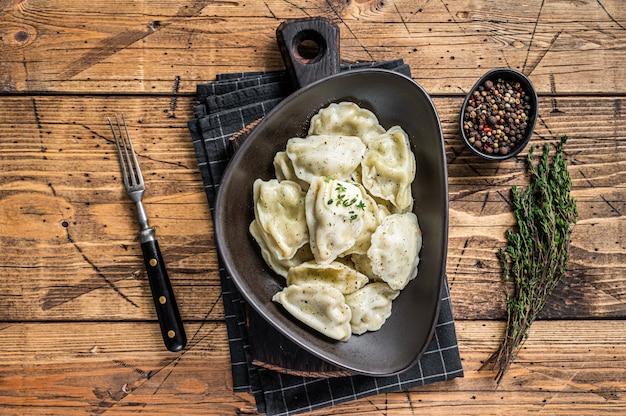 Pierogi de bolinhos de massa com batata em um prato com ervas e manteiga. mesa de madeira. vista do topo.