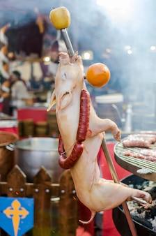 Pigget do assado em um mercado medieval, tortosa, espanha.
