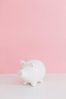 Piggybank branco na mesa branca sobre o fundo rosa