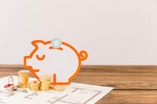 Piggybank com moedas empilhadas e chave na planta
