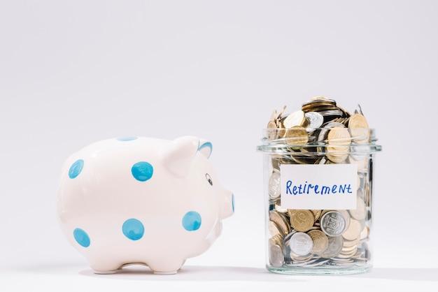 Piggybank perto de recipiente de aposentadoria cheio de moedas no pano de fundo branco