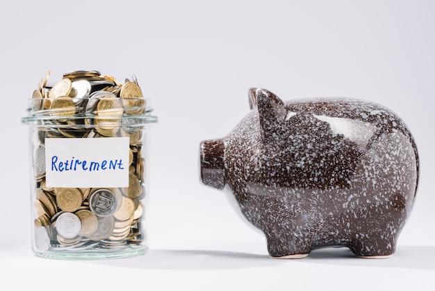 Piggybank perto de recipiente de vidro de aposentadoria cheio de moedas