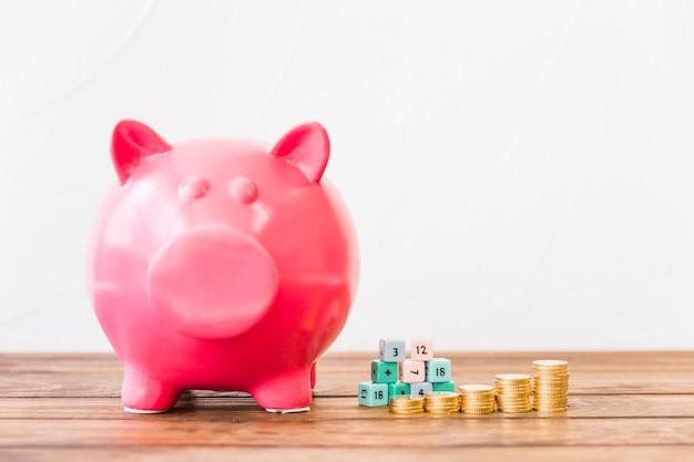 Piggybank rosa perto de moedas empilhadas e blocos de matemática