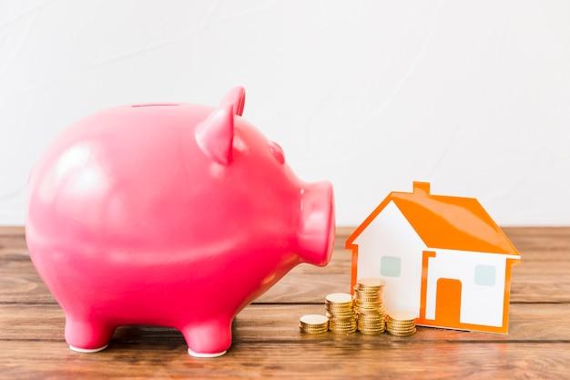 Piggybank rosa perto de moedas empilhadas e casa na mesa de madeira