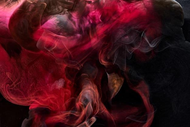 Pigmento preto vermelho rodando fundo abstrato de tinta, tinta de fumaça líquida debaixo d'água