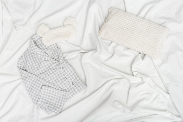 Pijama cinza, máscara de dormir, almofada macia e fofa no lençol amassado branco