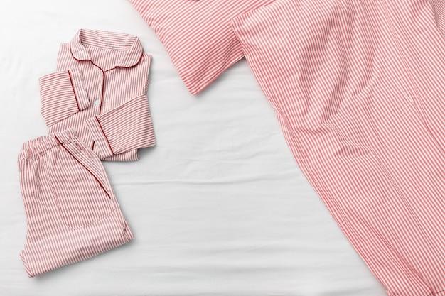 Pijama rosa dobrado cama, cobertor e travesseiro no quarto da casa.