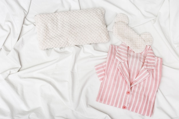 Pijama rosa, máscara de olho fofa para dormir e travesseiro macio na cama com pano de algodão branco