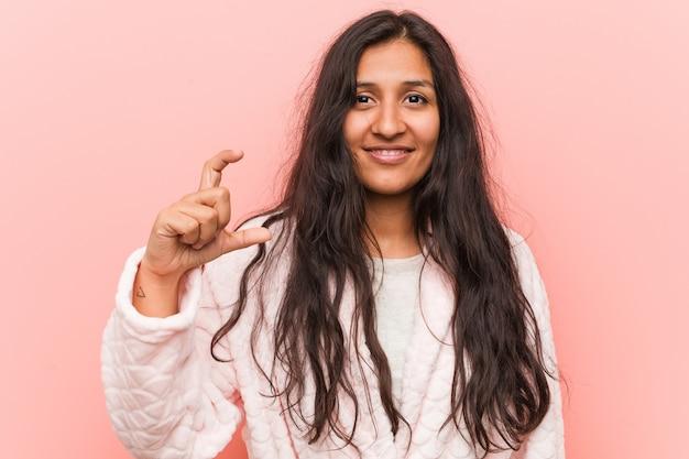Pijama vestindo da mulher indiana nova que guarda algo pouco com dedos indicadores, sorrindo e seguro.