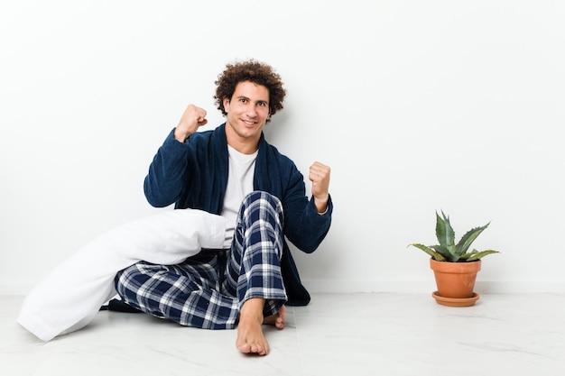Pijama vestindo do homem maduro que senta-se no assoalho da casa que levanta o punho após uma vitória, conceito do vencedor.