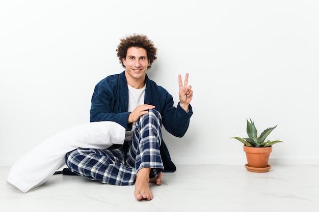 Pijama vestindo do homem maduro que senta-se no assoalho da casa que mostra o sinal da vitória e que sorri amplamente.