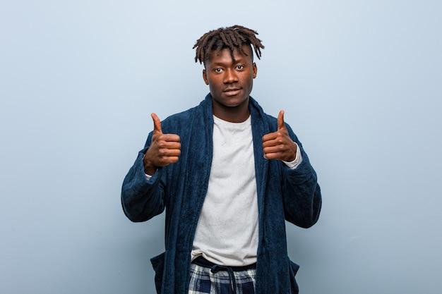 Pijama vestindo do homem negro africano novo que aumenta ambos os polegares acima, sorrindo e seguro.