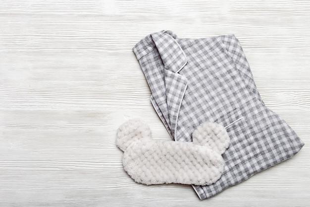 Pijamas mornos quadriculados cinzentos para mulheres e máscara de olho para dormir na superfície de madeira.