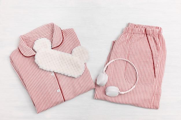 Pijamas para dormir. pijama de mulheres rosa com listras, camisa e shorts, fones de ouvido. máscara de dormir em madeira branca. copie o espaço. vista do topo. postura plana.