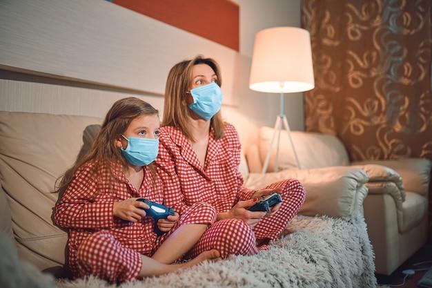 Pijamas vestindo da mulher e da moça e máscaras protetoras médicas que sentam-se no sofá na sala de visitas com quarentena do isolamento dos controladores do jogo de vídeo em casa auto, covid-19.