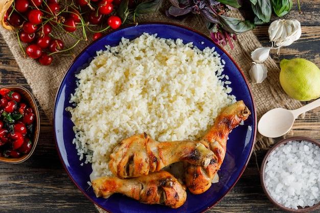 Pilaf com carne de frango, cereja, sal, limão, manjericão, alho em um prato na madeira e pedaço de saco.