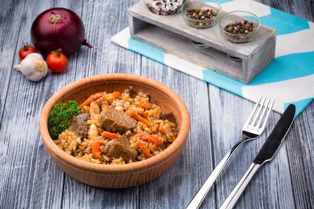 Pilaf com carne e cenoura na tigela de madeira