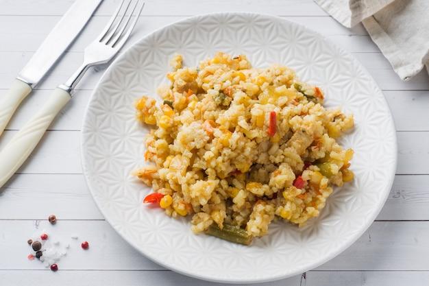 Pilaf com legumes e frango em um prato cinza em uma luz.