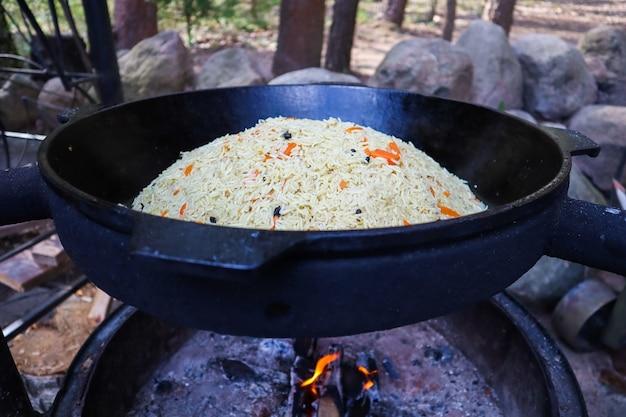 Pilaf de arroz em um grande caldeirão de ferro fundido em chamas