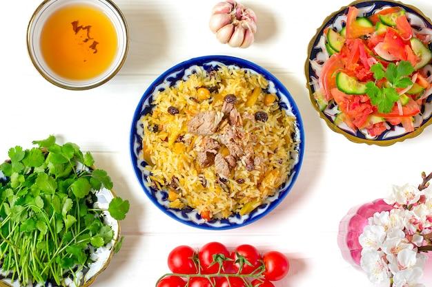 Pilaf nacional uzbeque com carne, salada achichuk de tomate, pepino, cebola em prato com padrão tradicional, coentro, tomate cereja na mesa de madeira branca