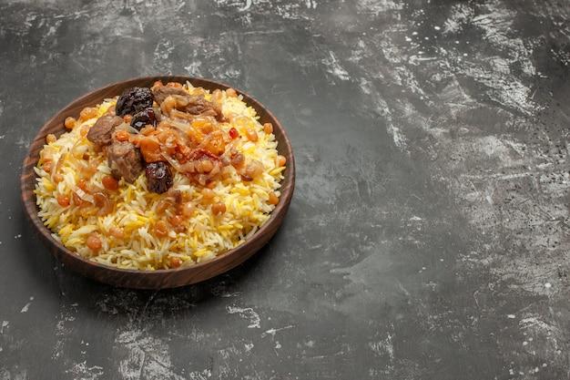 Pilaf tigela de madeira com frutas secas, arroz e carne na mesa