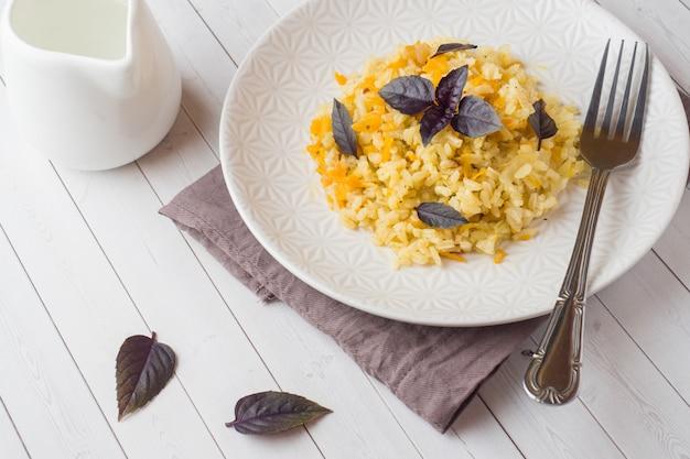 Pilaf tradicional, arroz com legumes e manjericão fresco em um prato em uma mesa de madeira clara.