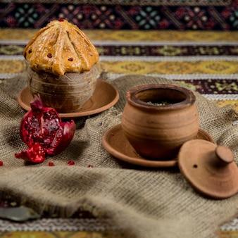 Pilaf tradicional em potes de barro sobre fundo de panos estampados