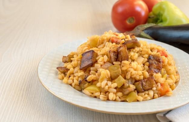Pilaf tradicional turco de bulgur, vegetais e berinjelas na mesa em um prato