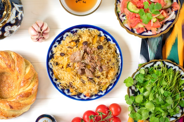 Pilaf uzbeque nacional com carne, salada achichuk de tomate, pepino, cebola no prato com padrão tradicional, coentro, tomate cereja, tortilla de pão de alho - patir na mesa de madeira branca