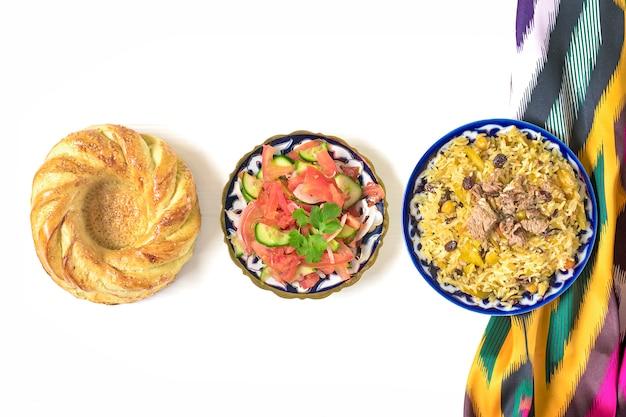 Pilaf uzbeque nacional com carne, salada achichuk de tomate, pepino, cebola no prato com tradicional
